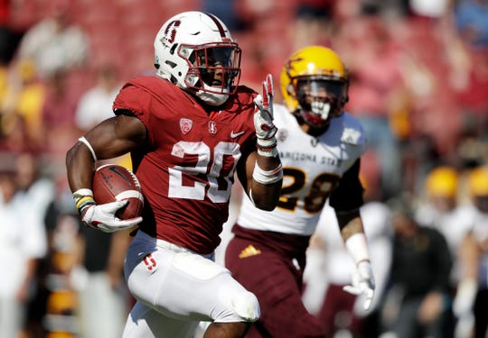FILE - In this Sept. 30, 2017, file photo, Stanford running back Bryce Love, left, runs for a touchdown past Arizona State defensive back Demonte King (28) during the third quarter of an NCAA college football game in Stanford, Calif. Love's unusual decision to return to school following a 2,000-yard rushing season that made him a Heisman Trophy runner-up will be validated in December when he walks on stage to receive the prize he came to Stanford to earn. Sure, the Heisman would be great but Love's decision to bypass the draft and play his senior year for the Cardinal was made to earn his degree in human biology. (AP Photo/Marcio Jose Sanchez, File)