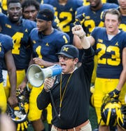 "Michigan head coach Jim Harbaugh leads his players and fans in singing ""Hail to the Victors"" after a preseason open practice session by the NCAA college football team at Michigan Stadium in Ann Arbor, Mich., Sunday, Aug. 26, 2018. (AP Photo/Tony Ding)"