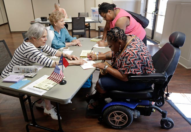 Adrienne Gray, bottom right, and Sherrisha Samples, top right, sign in to vote with help from poll workers Alice Gallagher, top left, and Sue Dickson, bottom left, at a polling place in Charlotte, N.C.