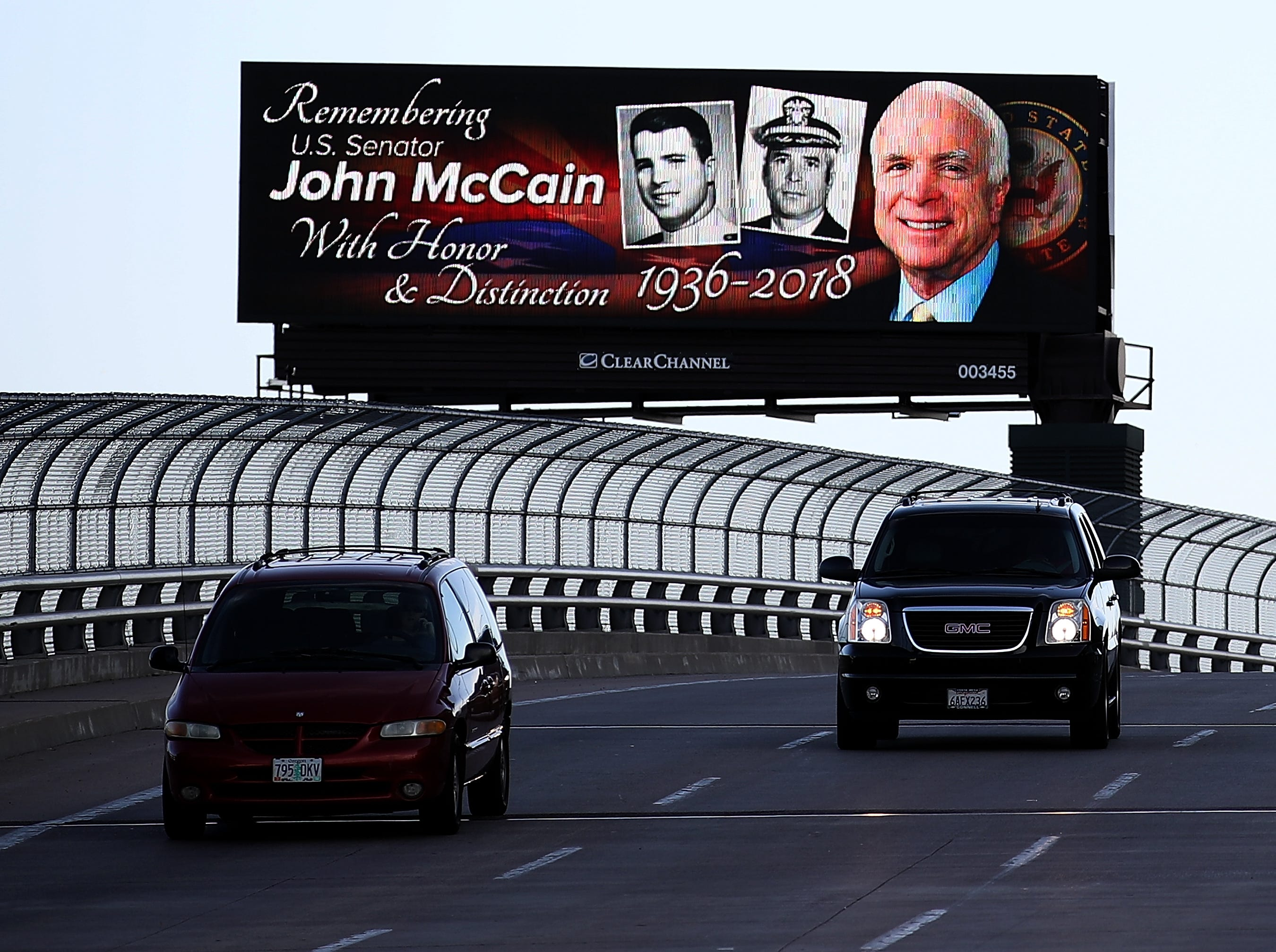 Cars drive by a billboard with a message honoring U.S. Sen. John McCain on Aug. 27, 2018 in Phoenix, Ariz.