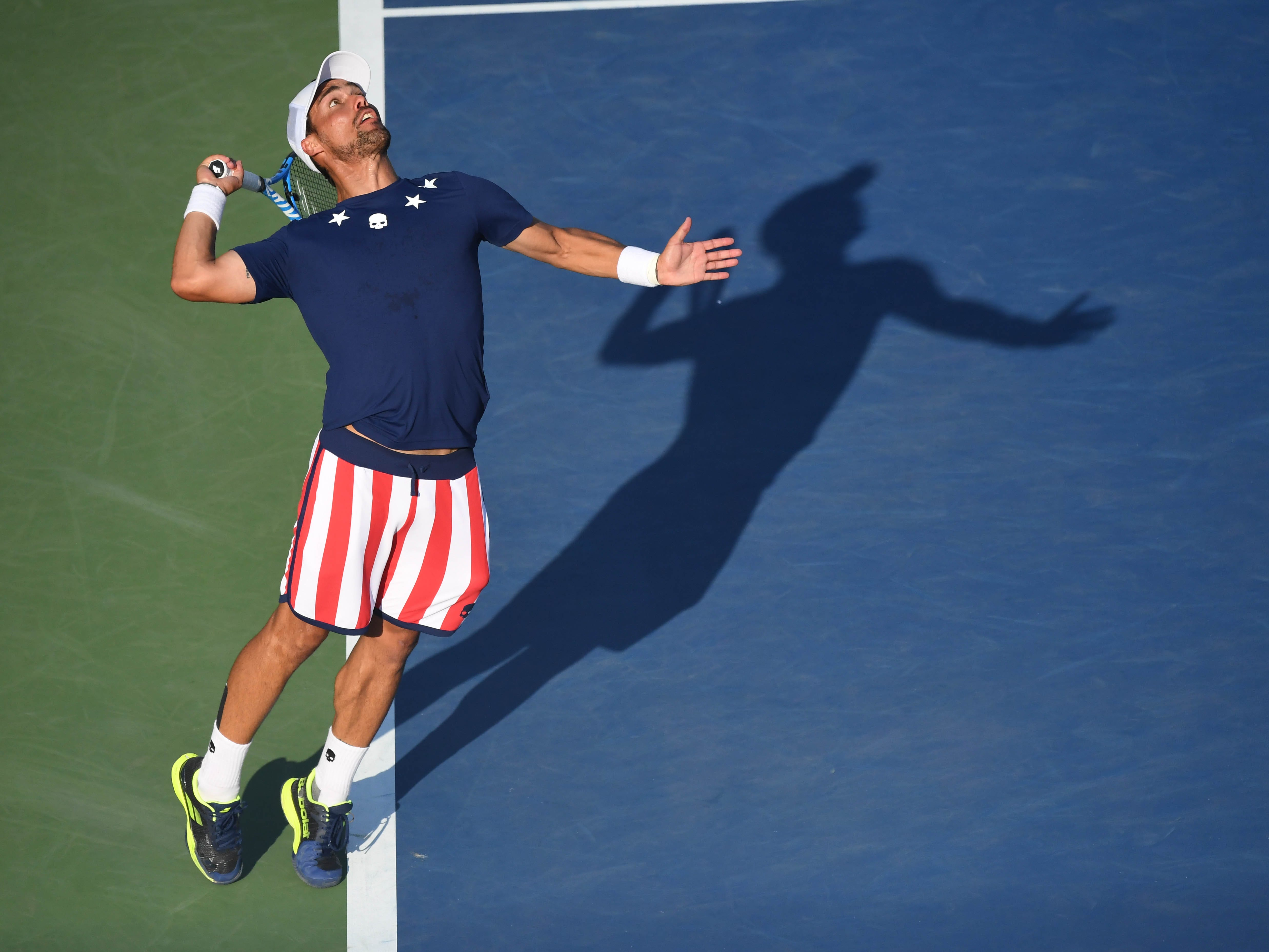 Fabio Fognini of Italy, decked out in stars and stripes, serves to Michael Mmoh of the USA. Fognini won 4-6, 6-2, 6-4, 7-6(4).