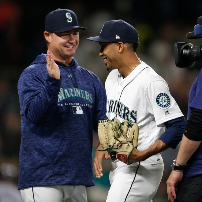 Seattle Mariners manager Scott Servais, left, congratulates Edwin Diaz after closing out a June victory over the Tampa Bay Rays.
