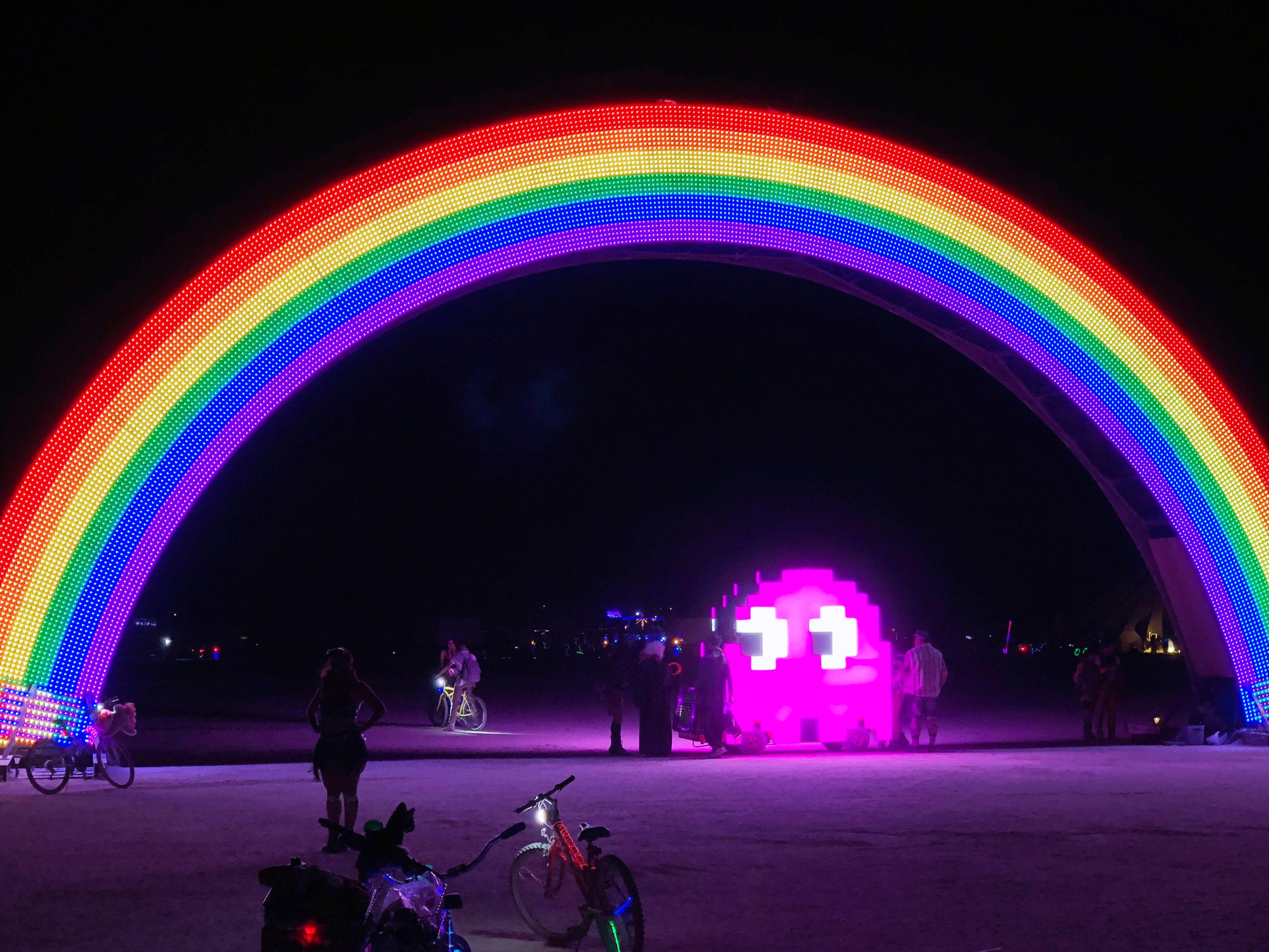 A ghost from PAC-MAN cruises beneath an illuminated rainbow bridge at Burning Man.