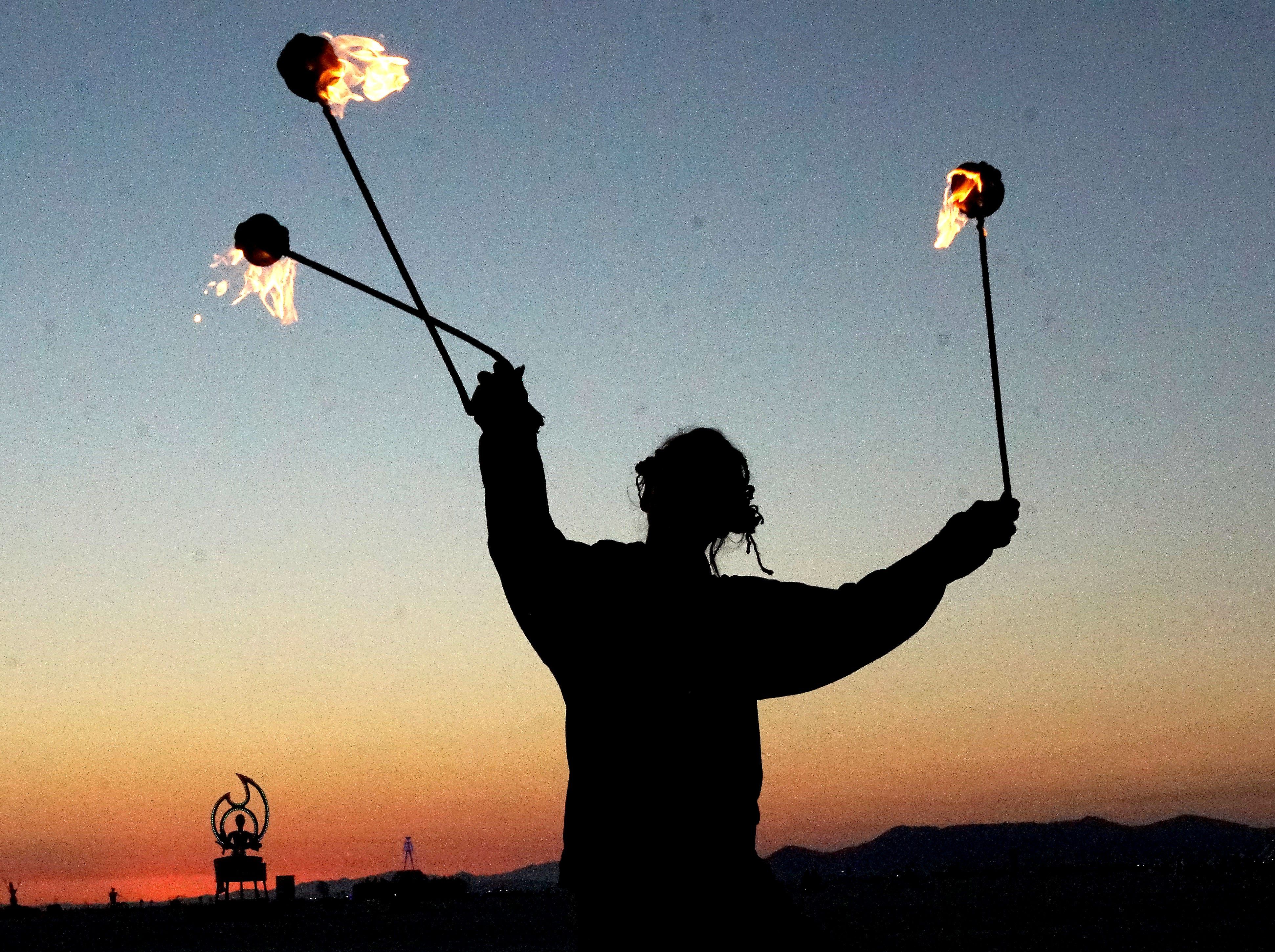 "A Burning Man participant who goes by the name ""Fractal"" spins flaming balls during the pre-dawn darkness."