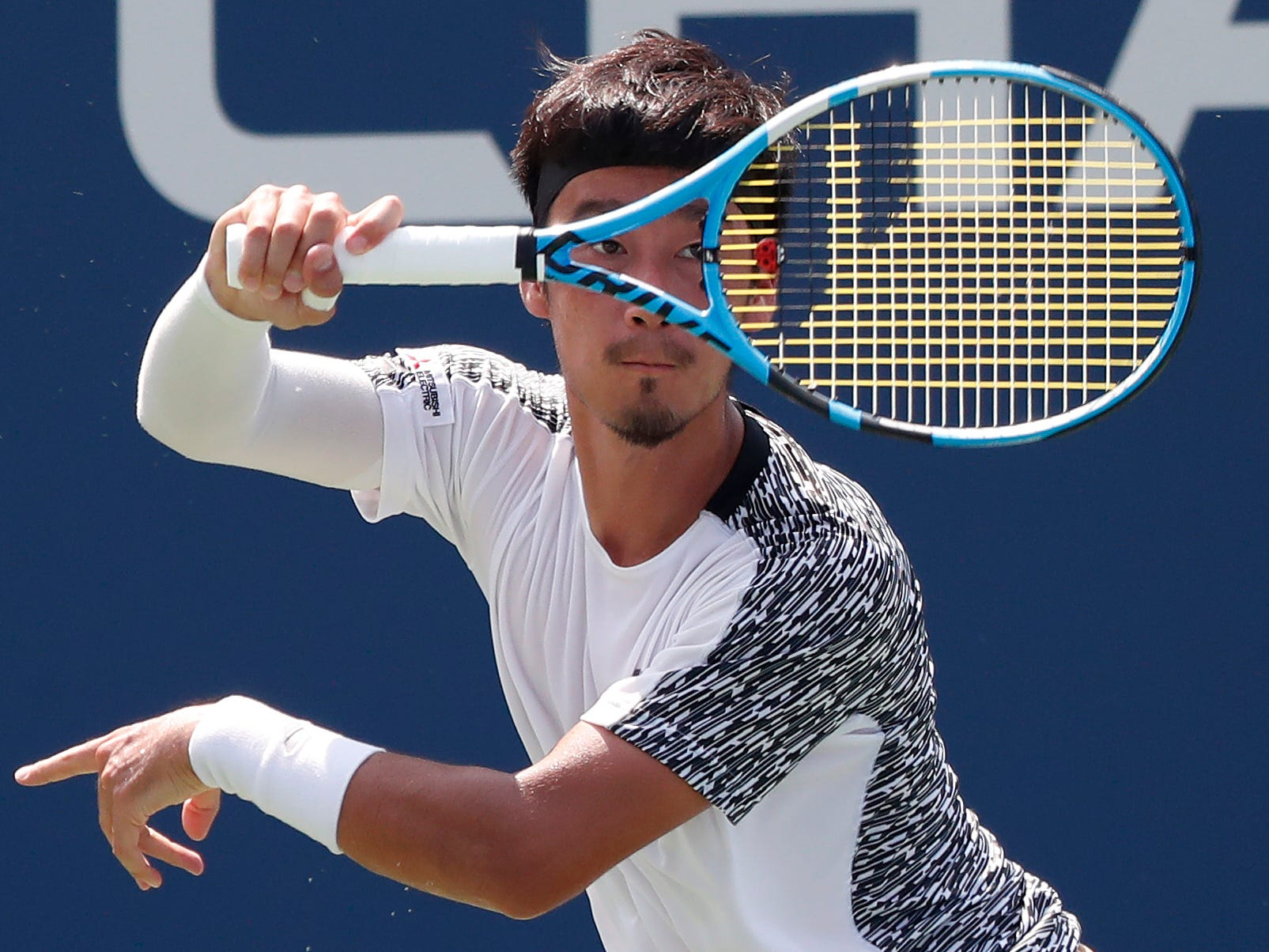 Yuichi Sugita of Japan hits a forehand against Richard Gasquet of France.
