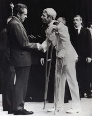 U.S. Navy Lt. Cmdr. John McCain is greeted May 25, 1973, by President Richard Nixon, left, in Washington, after McCain's release from a prisoner of war camp in North Vietnam.