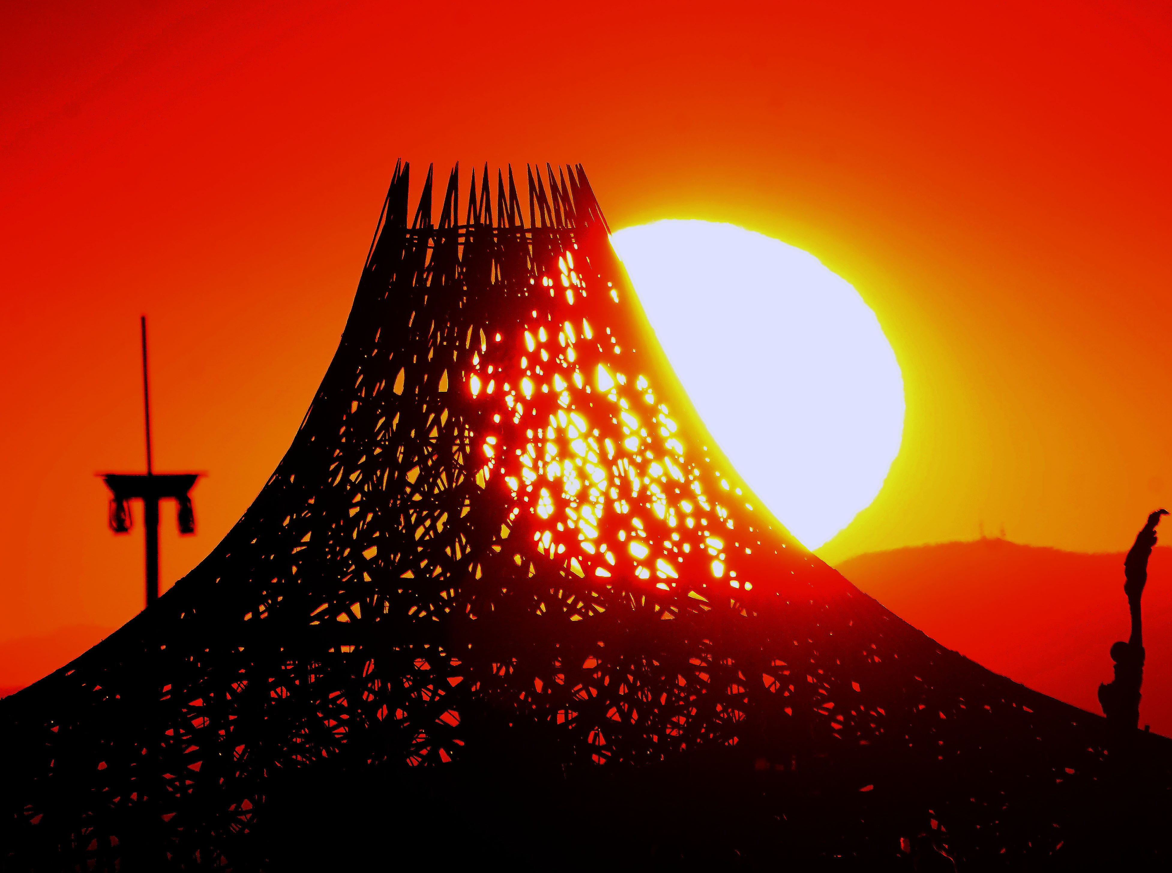 The morning sun rises above the horizon to illuminate the wooden Temple building at Burning Man.