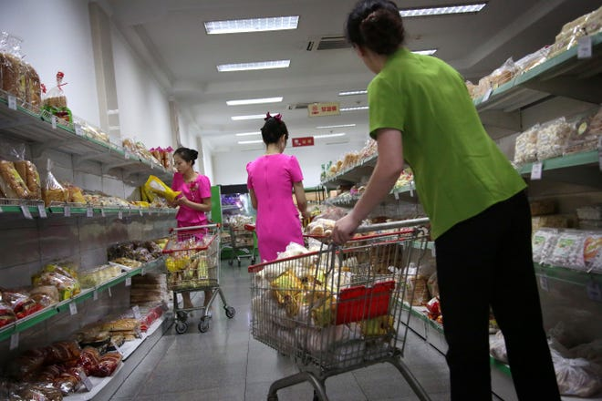 In this Monday, June 19, 2017, photo, staff at the Potonggang department store stock shelves with local and imported snacks, mostly from China, in Pyongyang, North Korea. Three generations into Kim Jong Un's ruling dynasty, markets have blossomed and a consumer culture is taking root.