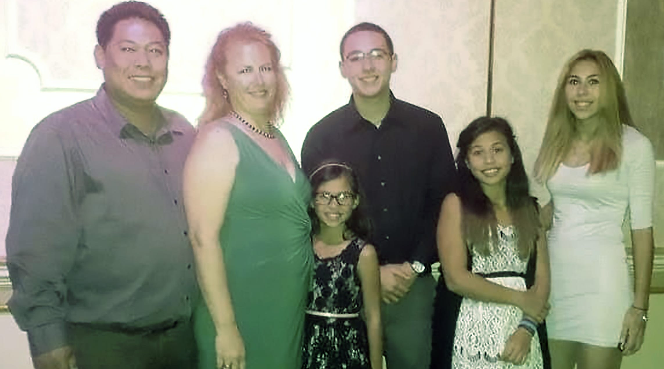 Cloyd Edralin, left, a green card holder who has lived in the U.S. for 30 years, is pictured next to his wife, Brandi Davison-Edralin, and their four children ages 11 to 22.