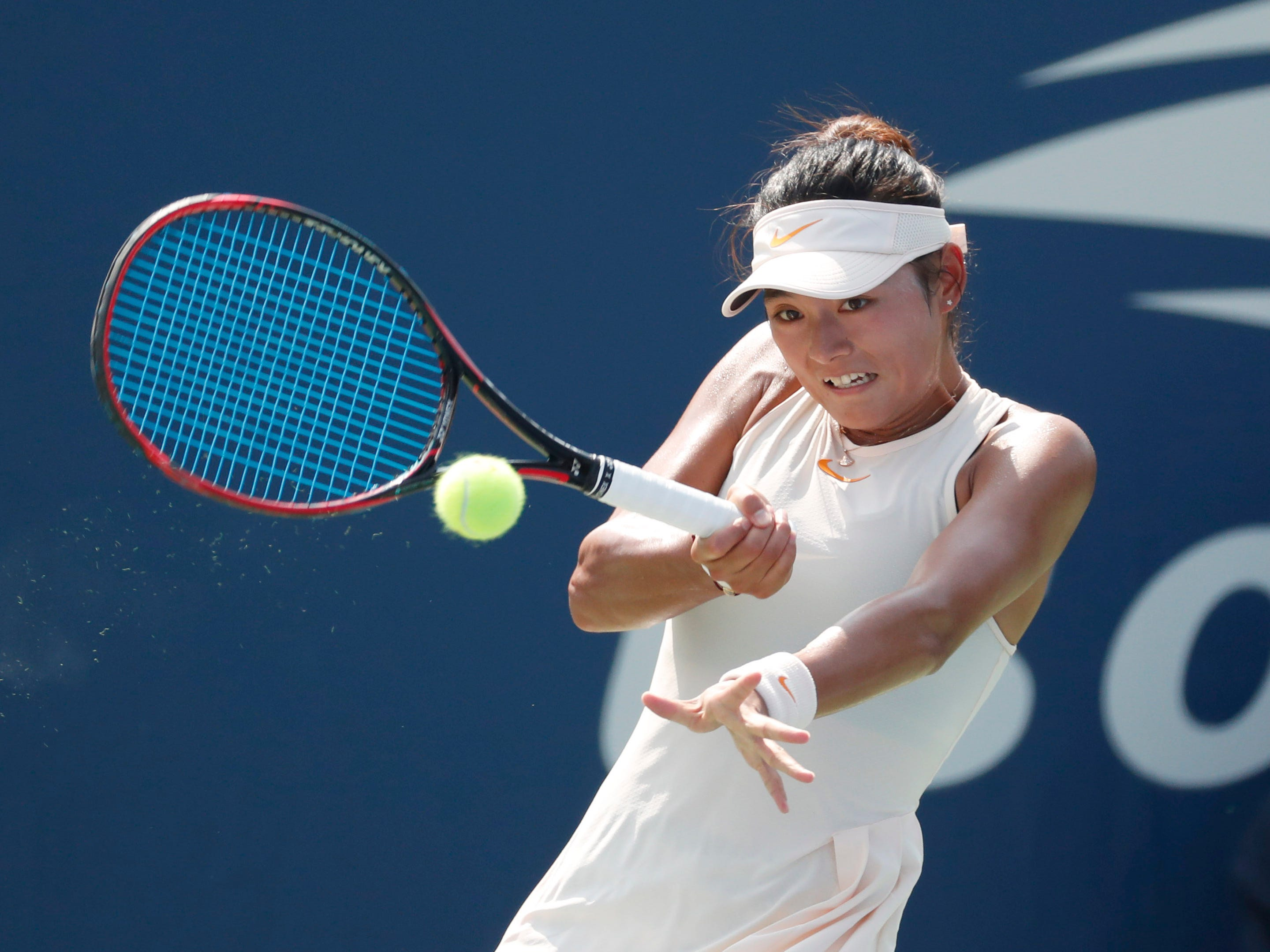 Yafan Wang of China returns a shot against Anna Karolina Schmiedlova.