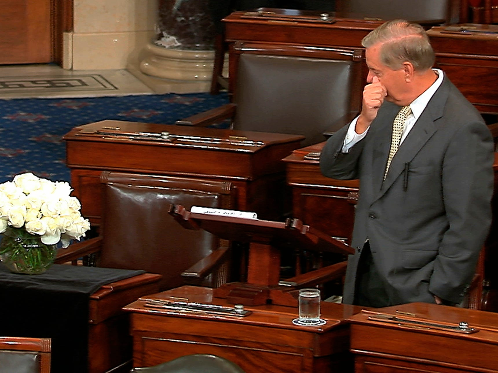 In this image from Senate Television, Sen. Lindsey Graham, R-S.C., pauses as he speaks on the Senate floor at the Capitol in Washington, on Tuesday, Aug. 28, 2018, next to the desk of Sen. John McCain, R-Ariz., draped in black with a bowl of white roses sitting on it. McCain died on Aug. 25, after battling brain cancer. Graham was McCain's best friend in the Senate.