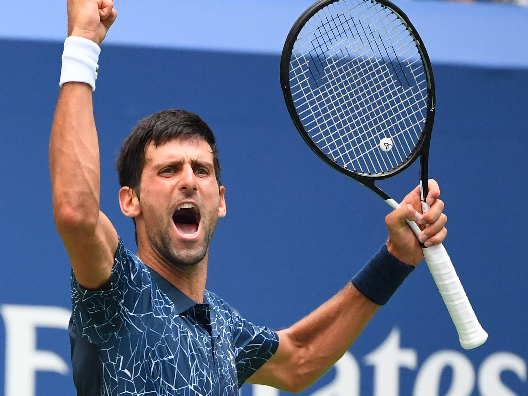 Novak Djokovic of Serbia celebrates winning the third set against Marton Fucsovics of Hungary.