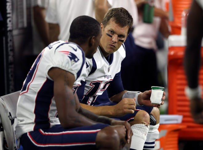 New England Patriots quarterback Tom Brady (12) speaks with wide receiver Malcolm Mitchell (19) on the bench during the game against the Houston Texans at NRG Stadium.