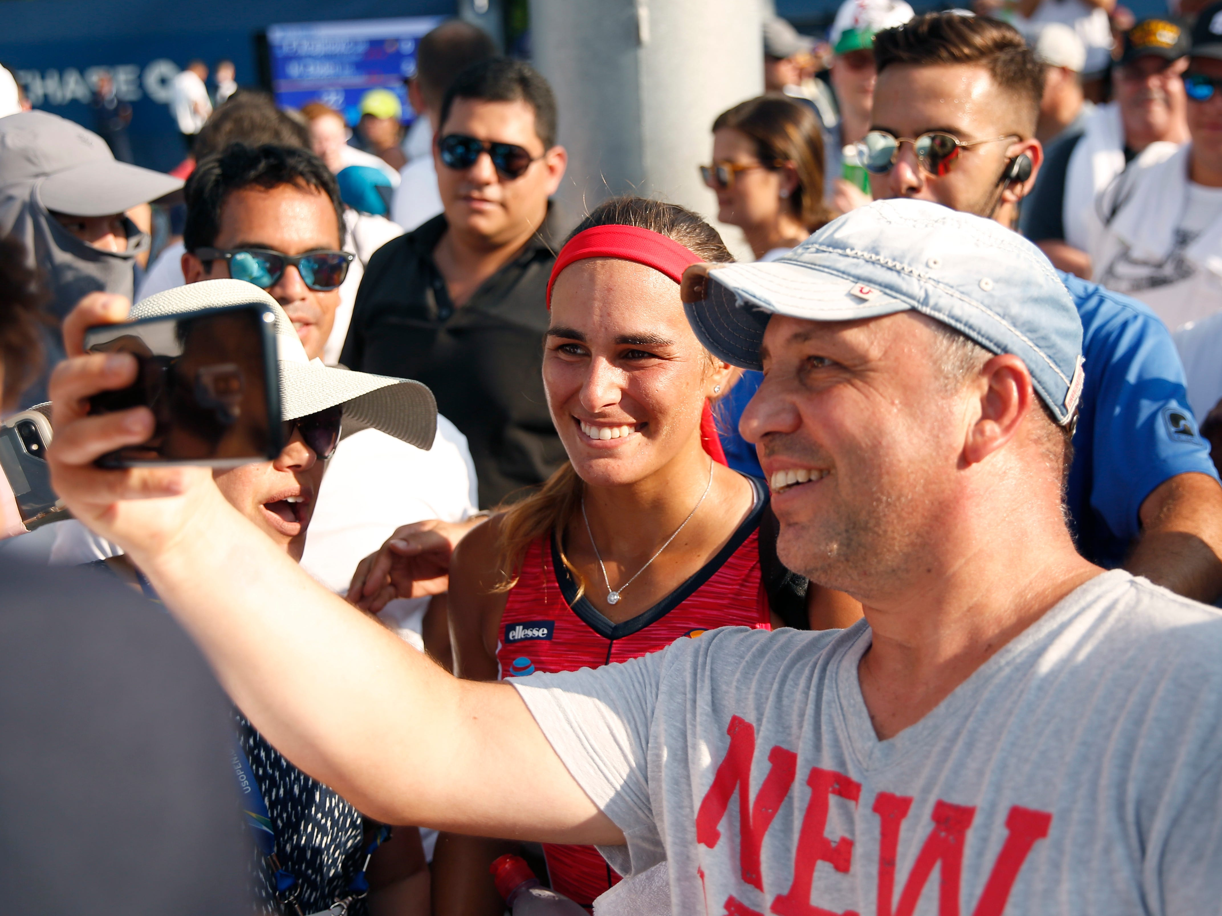 Monica Puig of Puerto Rico poses for a selfie with a fan after defeating Stefanie Voegele of Switzerland 6-0, 6-0.