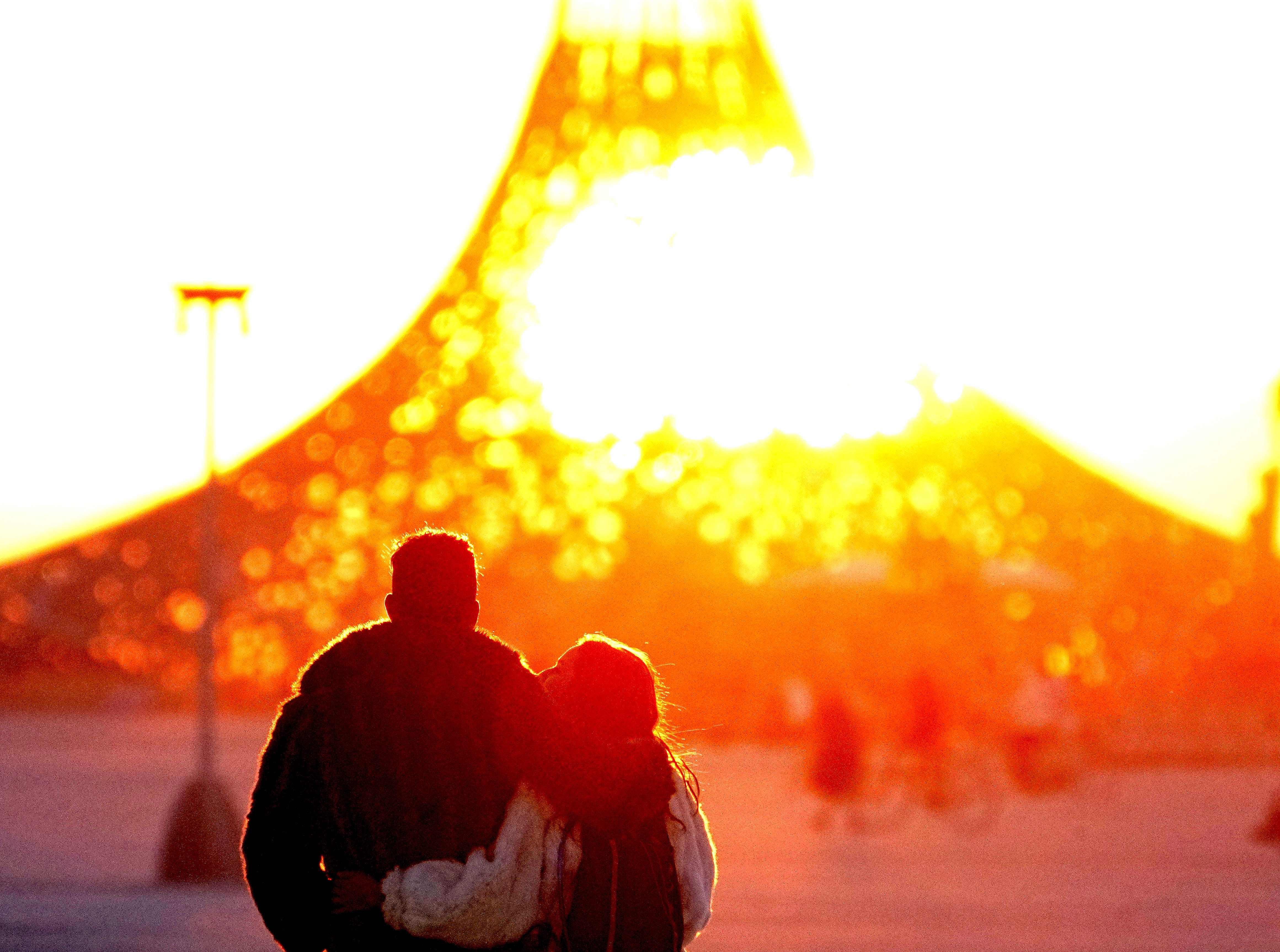 A couple embraces as they watch the sun rise through the Burning Man temple.