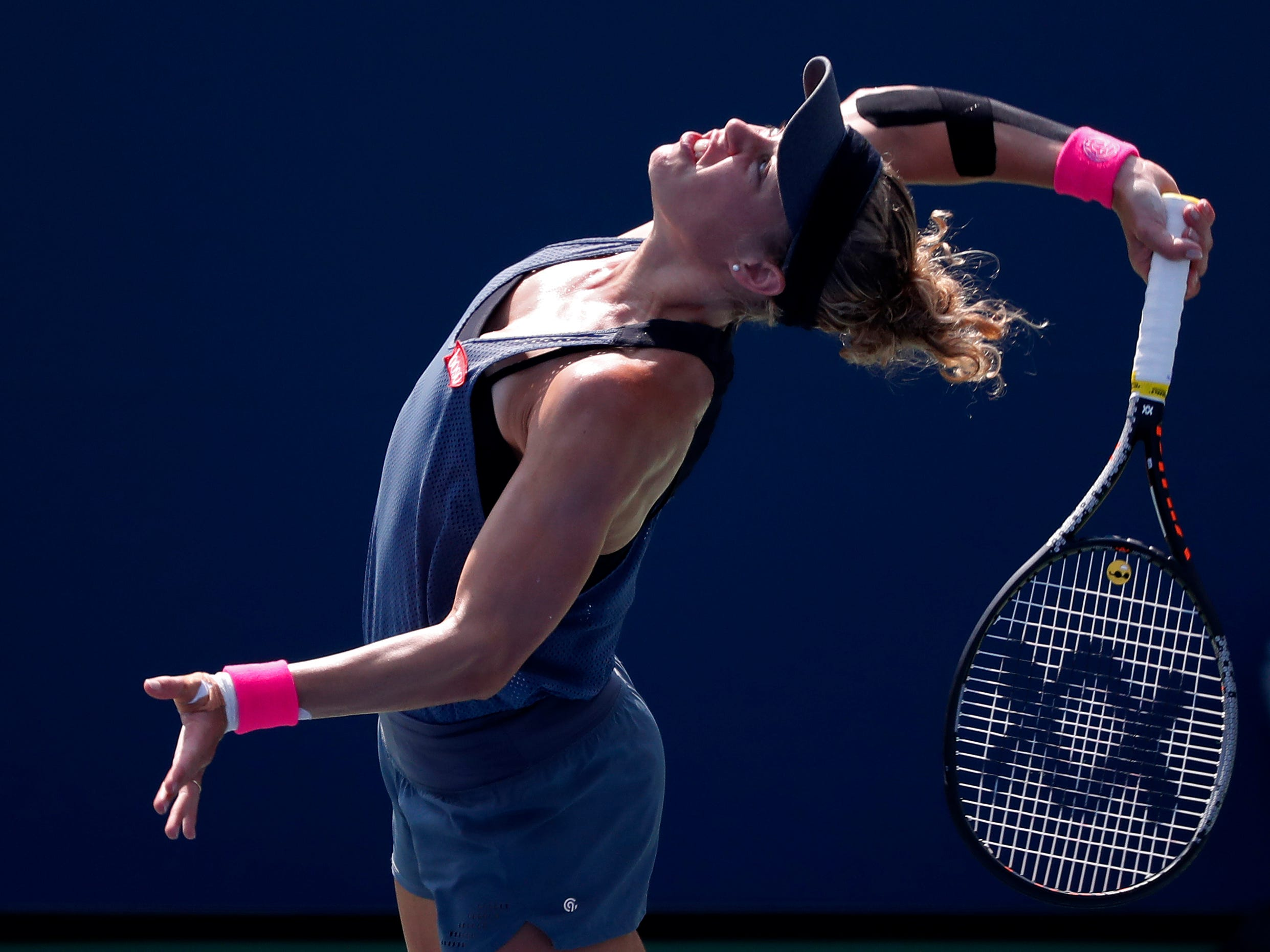 Laura Siegemund of Germany serves against Naomi Osaka of Japan.