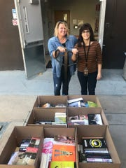 Crystal Patriarche, left, is shown here with 1,000 books her PR firm SparkPoint Studios to libraries in Arizona.