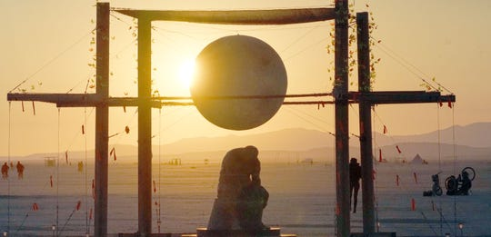 The morning sun illuminates a piece of art, which depicts a seated man beneath a globe, at Burning Man.