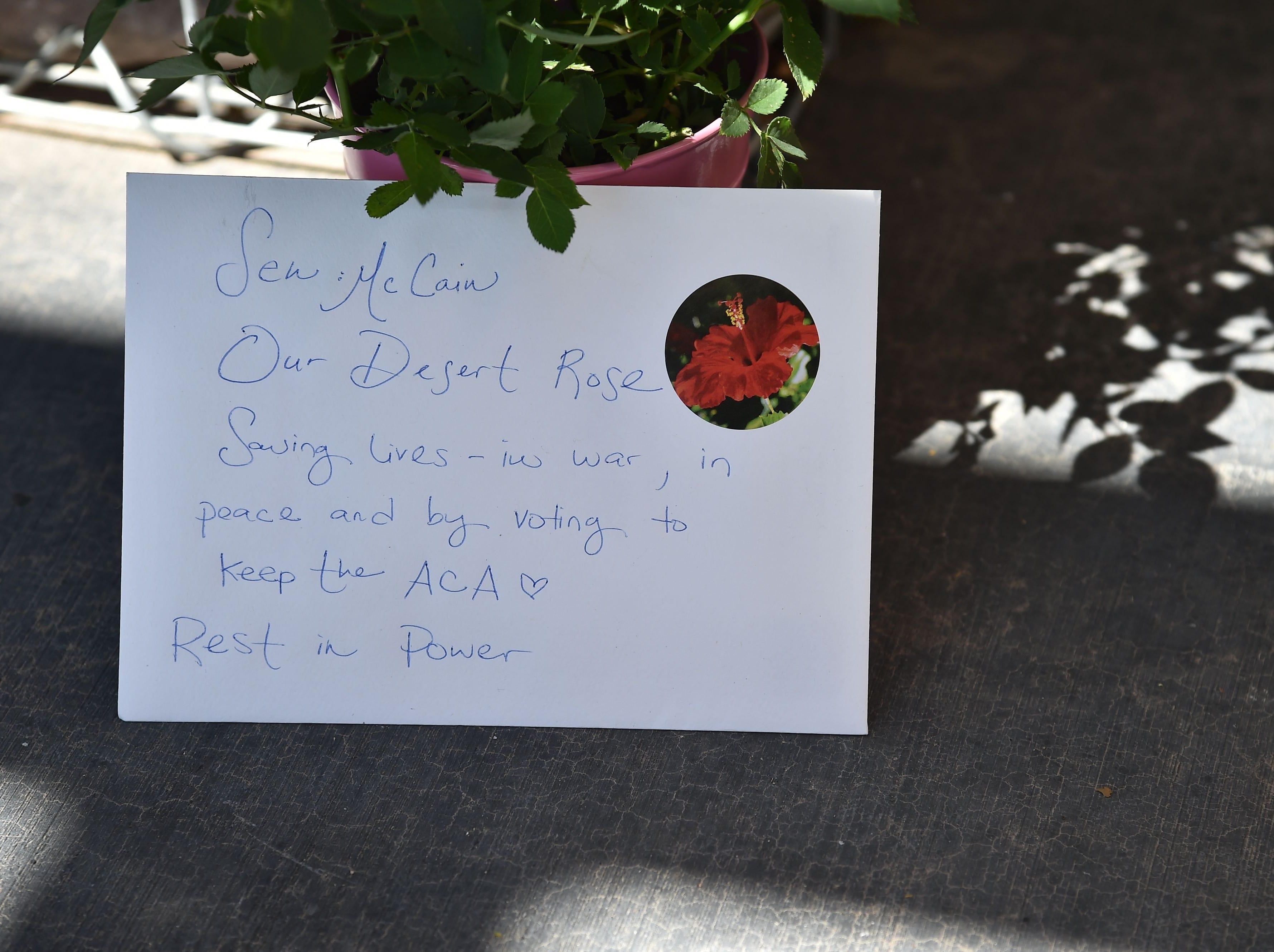 A handwritten note is seen at a makeshift memorial remembering Senator John McCain outside McCain's office in Phoenix, Ariz. Aug. 27, 2018.