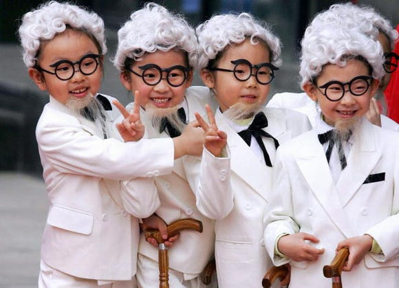 Young children in Beijing dress up as US fast-food chain Kentucky Fried Chicken's Colonel Sanders look-alikes during a store opening ceremony in Beijing in 2006.