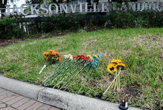 Flowers and a candle are left at the The Jacksonville Landing complex on Aug. 28, 2018, in Jacksonville, Fla. The complex reopened to the public Tuesday after three people were killed Sunday, including the gunman, at a video game tournament.