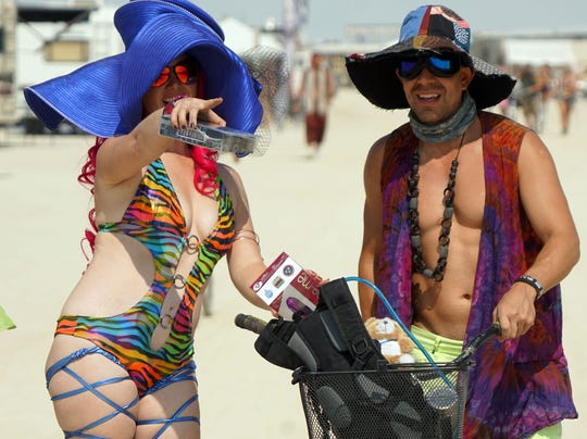 Chelsi Linderman of Pleasant Grove, Utah, gives directions to a passerby outside her camp at Burning Man.