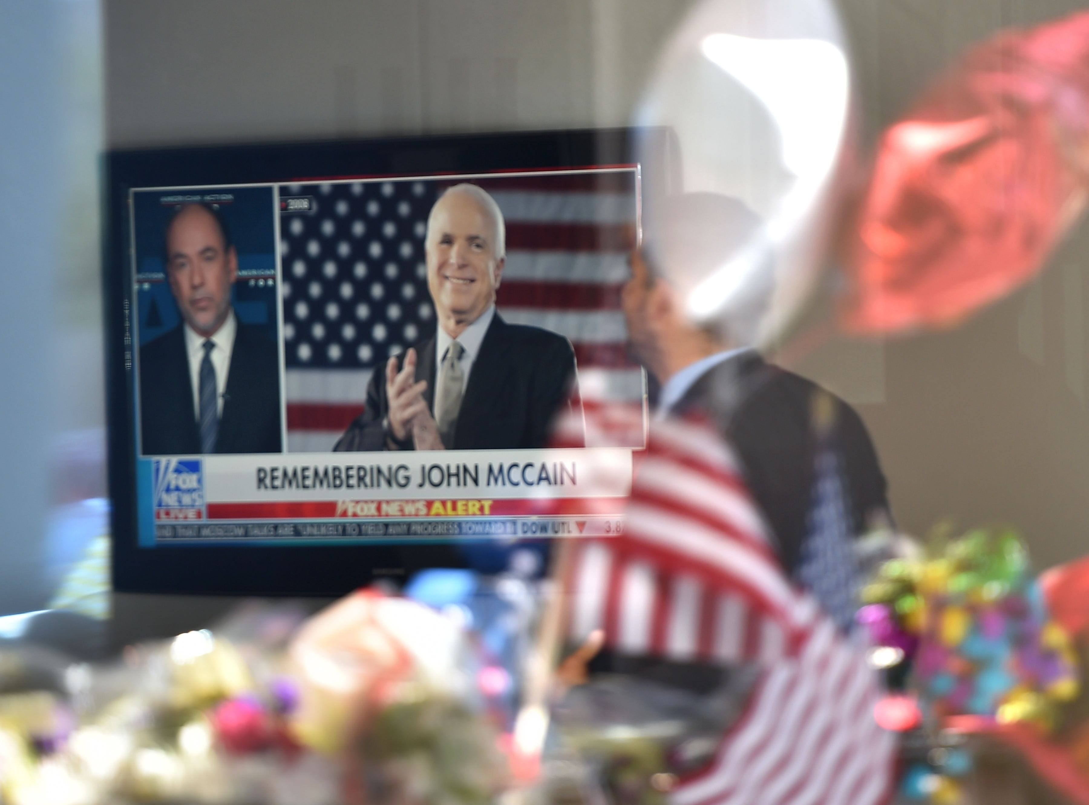 A man in the lobby of Senator John McCain's former office building watches a Fox News report as flowers and balloons from a makeshift memorial located outside the building are reflected in the building's glass window, Aug. 27, 2018 in Phoenix, Ariz.