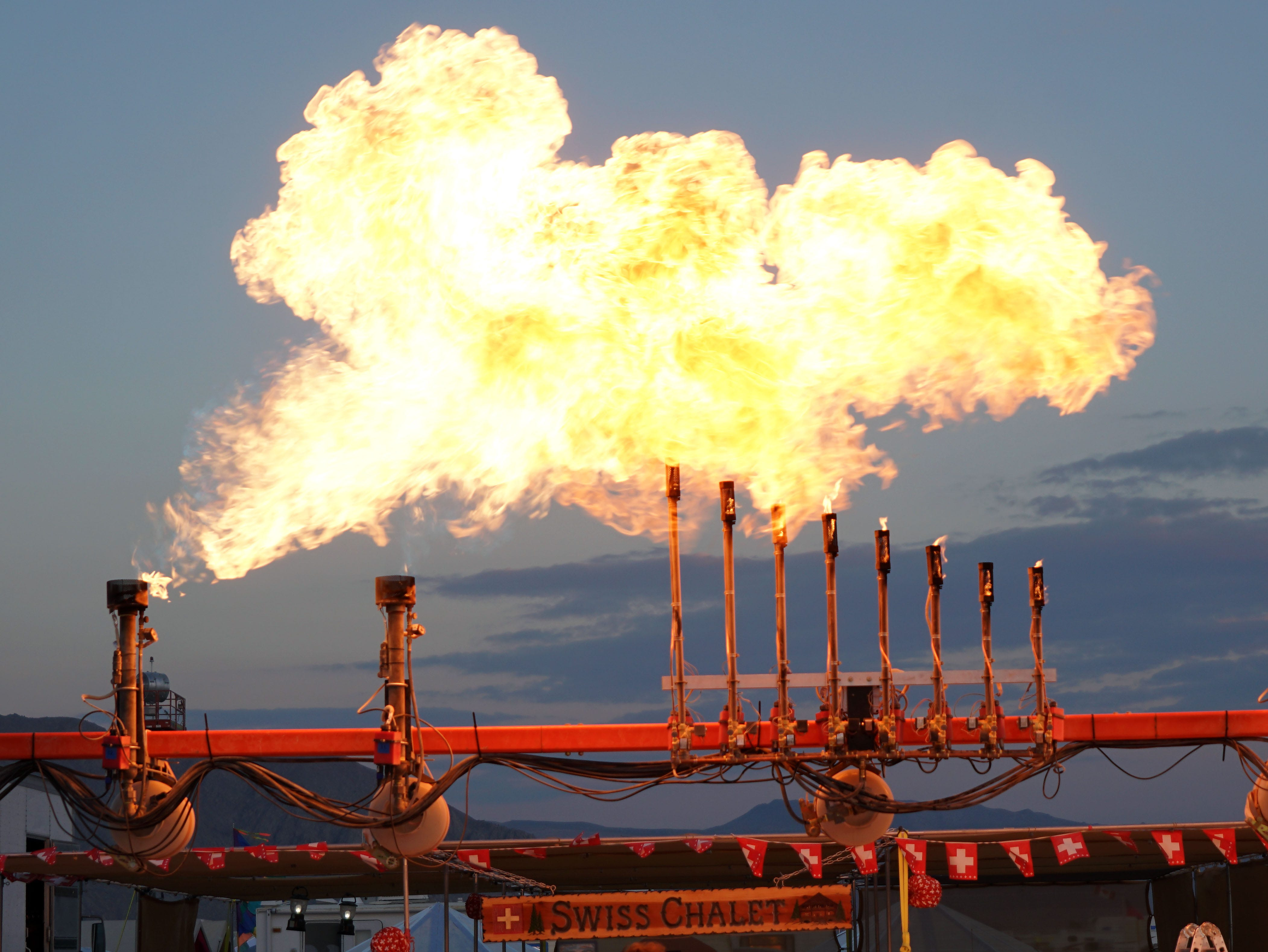 A Burning Man participant watches as an art installation belches fire. Propane-powered flamethrowers are a popular item to install on vehicles and art pieces at Burning Man.