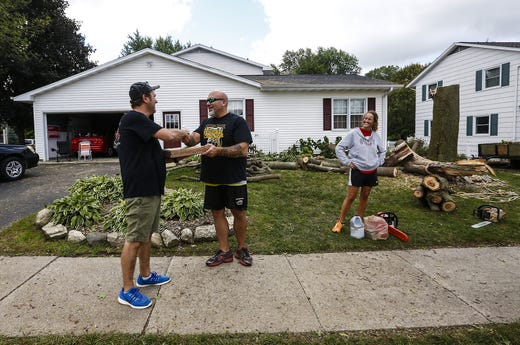 Tony Evola's Pizza throws a pizza at Jason and Kelly Hraban on Wednesday, August 29, 2018 as they clear a tree their favorite is the house in Waupun, Wisconsin. Evola drove around Waupun, distributing pizzas to the people affected by the heavy weather that spread across the Waupun area on Tuesday afternoons. Doug Raflik / USA TODAY NETWORK-Wisconsin
