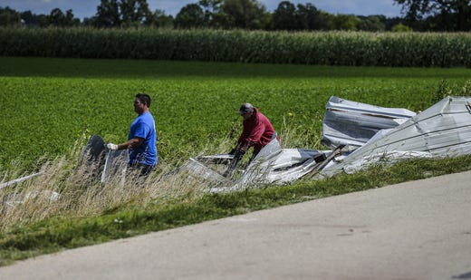 Ben Brown of DeForest and David Schwandt of Markesan help to erase sheet metal from a field Wednesday, August 29, 2018, at W12072 Hemp Road near Waupun, Wisconsin , Heavy weather hit the Waupun area, causing major damage on Tuesday afternoons and affecting a potential tornado in some places. Doug Raflik / USA TODAY NETWORK Wisconsin