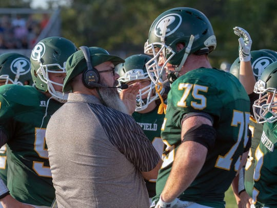 First-year Pennfield head coach Mike Clothier speaks to players during the first game of the season last week