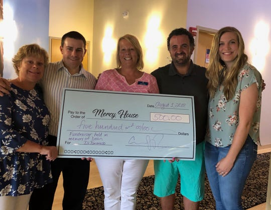 DJ Andy Papaleo, second from right, presents a check for $500 to the Mercy House of the Southern Tier.