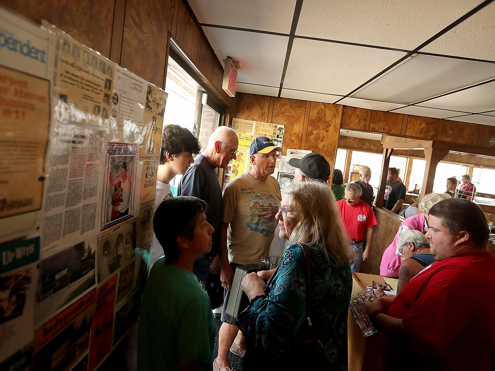 Rick Gehring (center) stands among the crowd as they enter and exit during a sports memorabilia giveaway and restaurant equipment sale at the A&W in Port Orchard on Wednesday, August 29, 2018.