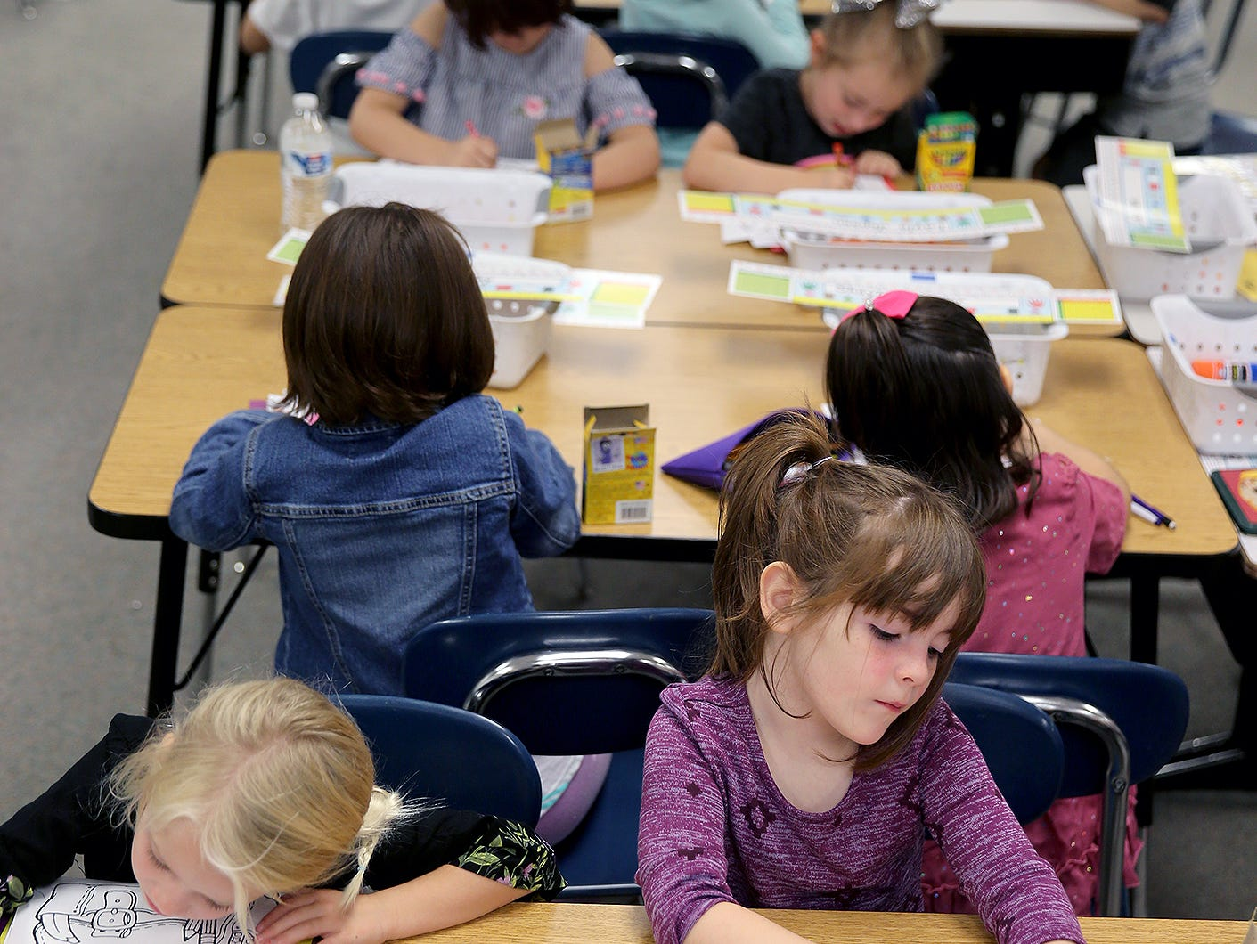 First graders Ensley Bakken, left, and Lucy Dempsey color during class.