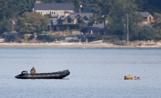 Navy divers attach a rope to an apparent mine adrift off Brownsville Marina on Tuesday.