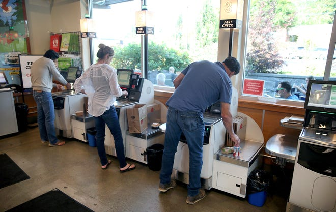 Customers use the new-self checkout station at the Town & County Market on Bainbridge Island.