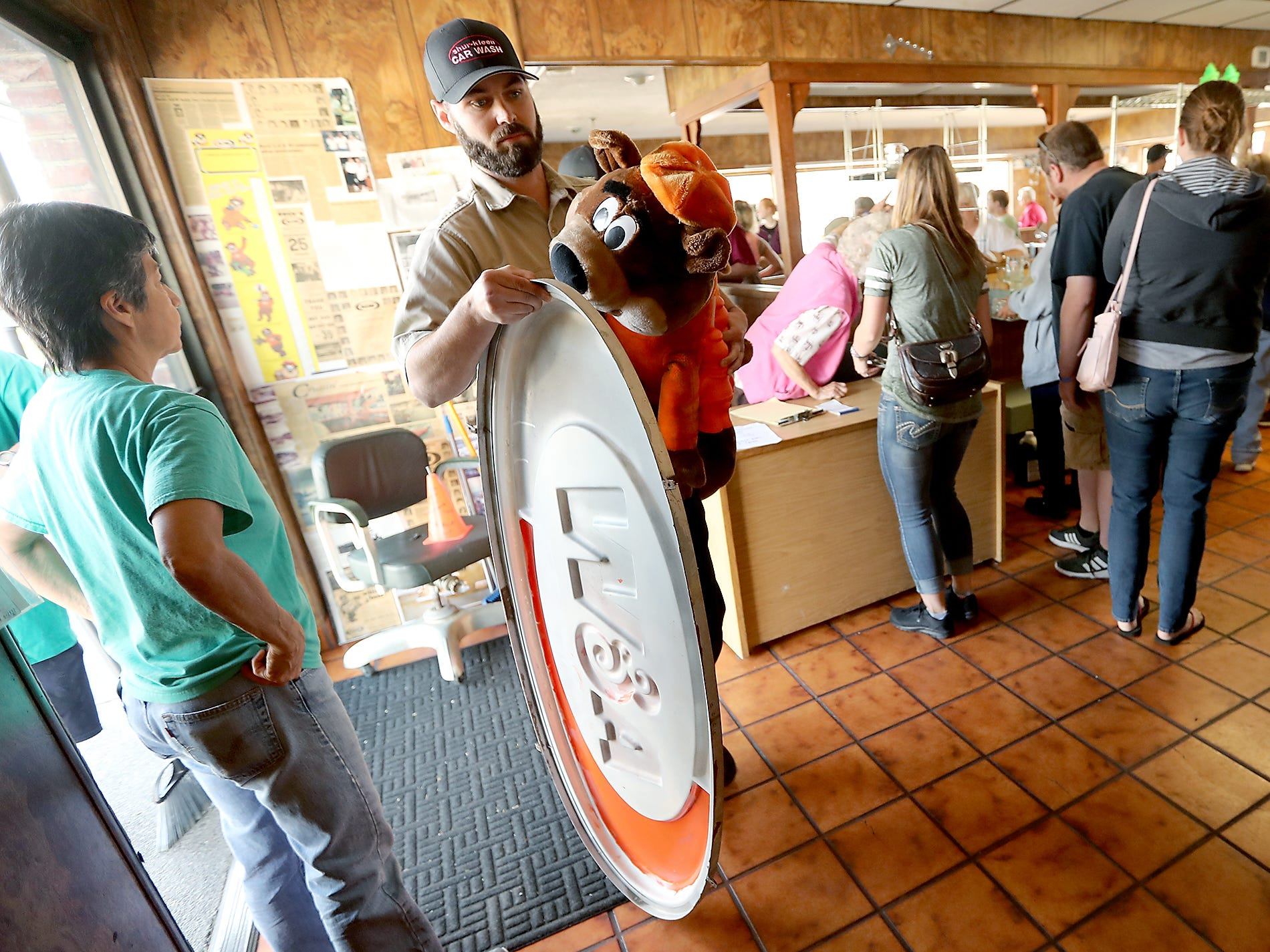Jonny Laing, of Lacy, carries an A&W sign and a stuffed Great Root Bear (the mascot for A&W Root Beer) as he heads for the checkout line during a sports memorabilia giveaway and restaurant equipment sale at the A&W in Port Orchard on Wednesday, August 29, 2018.