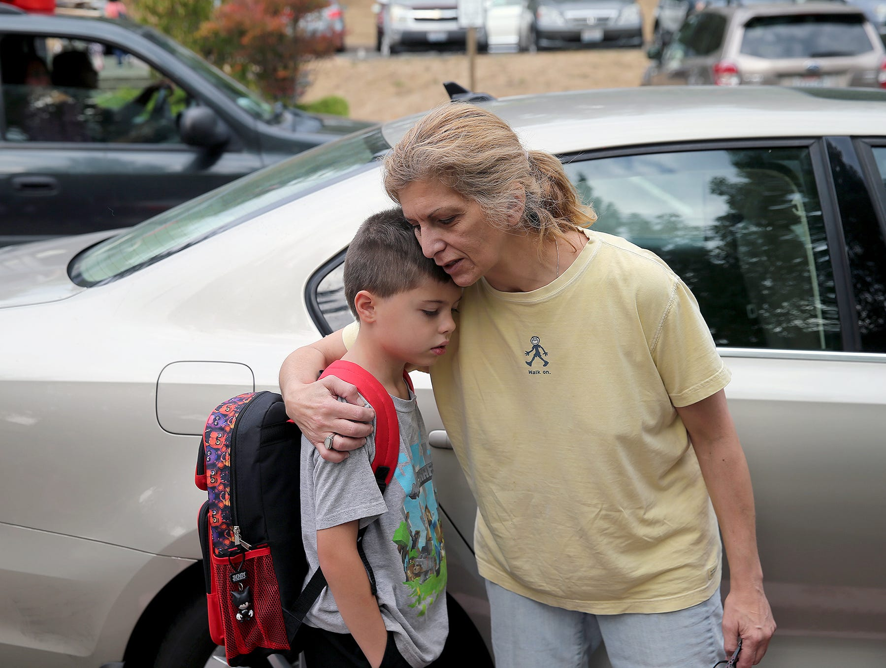 Crosby Egnatios-Schultz, 7, is comforted by his mom, Robyn Egnatios, as she drops the third-grader off for the first day of school at Kitsap Lake Elementary.
