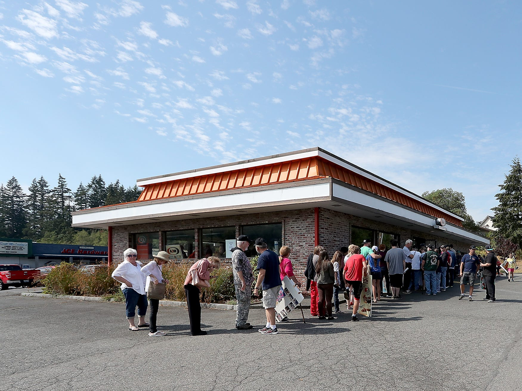 The line wraps around the building prior to the start of a sports memorabilia giveaway and restaurant equipment sale at the A&W in Port Orchard on Wednesday, August 29, 2018.