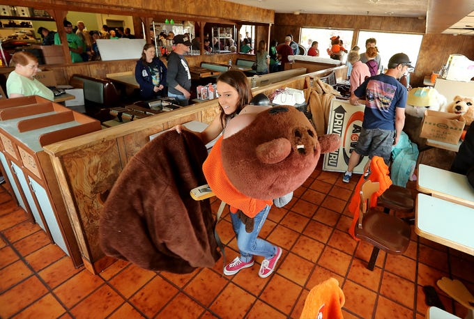 Melanie Zaccagnini, of Olalla, carries a Great Root Bear (also called Rooty who is the mascot for A&W Root Beer) costume to the checkout area during a sports memorabilia giveaway and restaurant equipment sale at the A&W in Port Orchard on Wednesday, August 29, 2018.