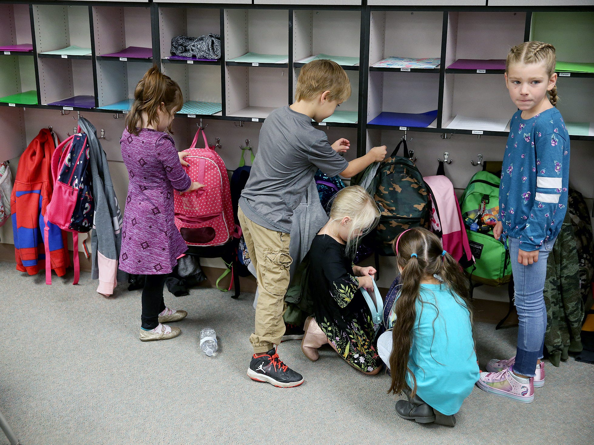First graders put away there backpacks on the first day of class at Kitsap Lake Elementary School on Wednesday.