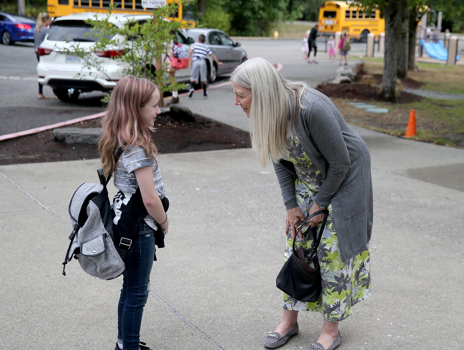 Kitsap Lake Elementary School principal Karen Rommen welcomes fourth-grader Kylee Starn on the first day of school on Wednesday.