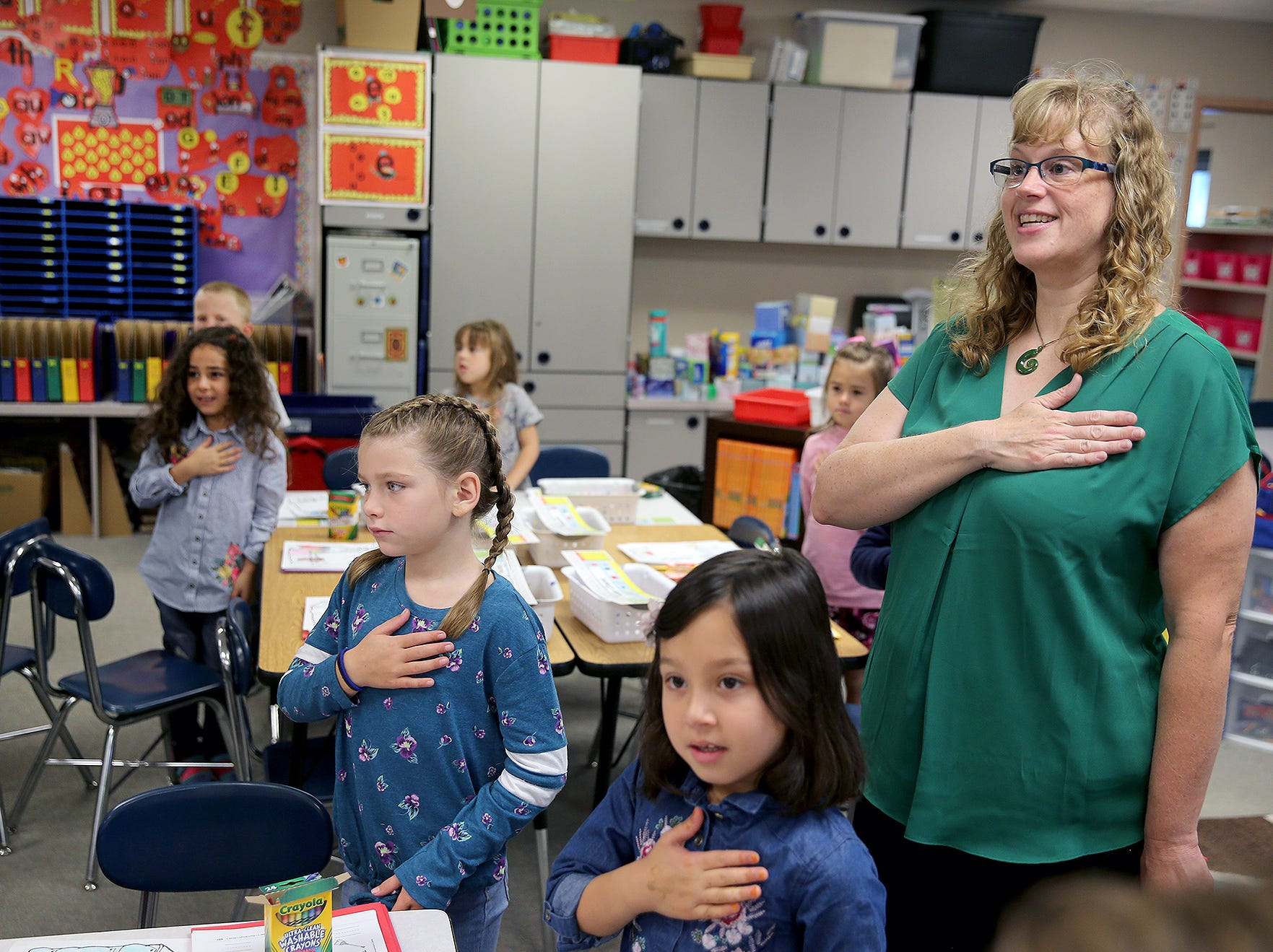 First grade teacher Becky Montgomery leads her students in the Pledge of Allegiance on the first day of class at Kitsap Lake Elementary School on Wednesday.