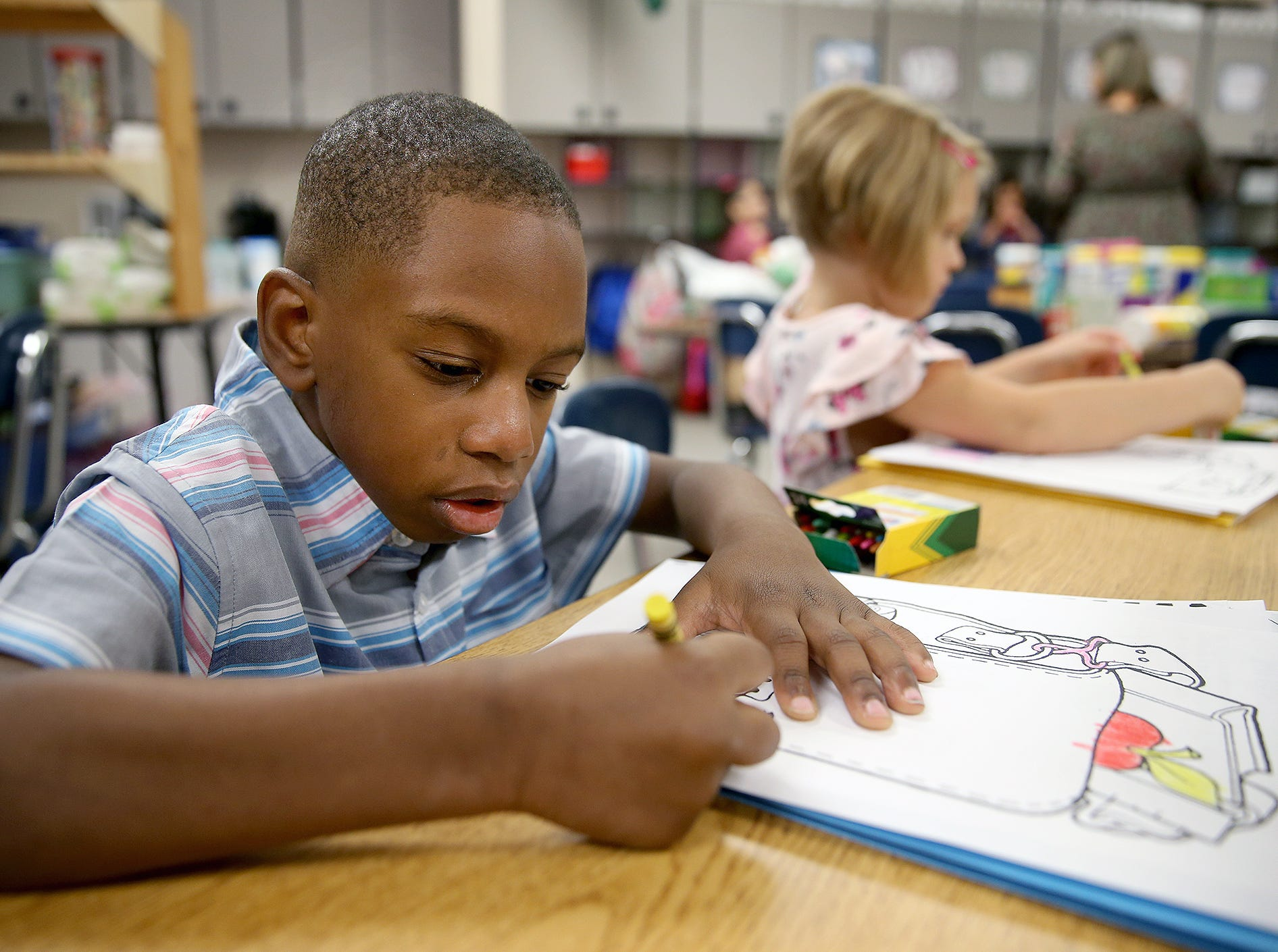 First grader Miles Prince colors on the first day of class at Kitsap Lake Elementary School.