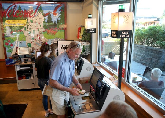 Craig Clark of Bainbridge Island uses the new-self checkout station at the Town & County Market on Bainbridge Island to pay for his sushi.