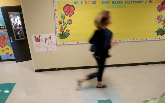 A Kingston Middle School staff member is a blur as she runs down the hall while participating in shooter drills at Kingston Middle School.