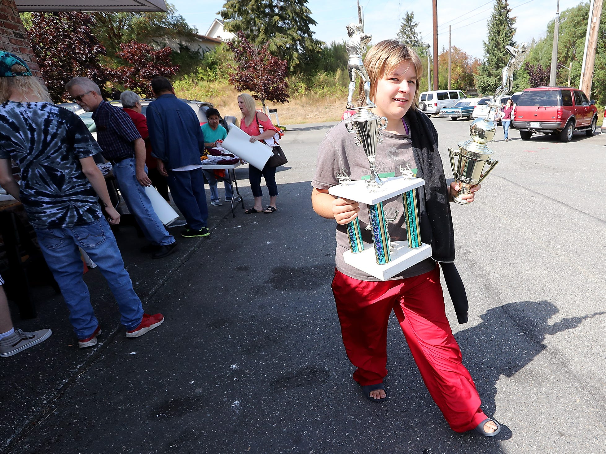 Skyann Gillett carries away two trophies during a sports memorabilia giveaway and restaurant equipment sale at the A&W in Port Orchard on Wednesday, August 29, 2018.