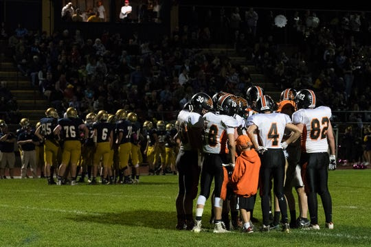 The teams huddle together during a time out during the high school football game between the Middlebury Tigers and the Essex Hornets at Essex High School on Octoer 7, 2016.
