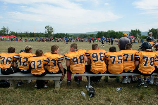 Player sit on the bench during the youth football jamboree at the Palmer Field on Saturday afternoon August 25, 2018 in Hinesburg.