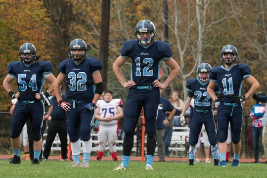 MMU quarterback Asa Carlson (12) looks to the sidelines for a play during the high school football game between the Hartford Hurricanes and the Mount Mansfield Cougars at MMU High School on Saturday afternoon October 14, 2017 in Jericho.